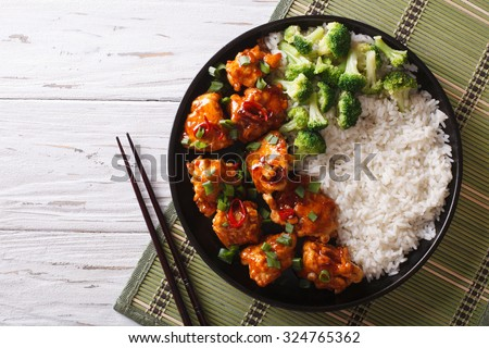 Tso's chicken with rice, onions and broccoli on the table. horizontal view from above