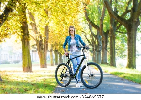 young happy smiling blonde beautiful woman wearing in white jeans riding bikes in park in bright sunlight on summer day #324865577