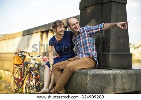 Young happy couple sitting on a old summer promenade. #324909200