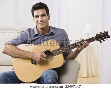 An attractive and relaxed looking man sitting on a couch and playing the guitar.  He is smiling at the camera. Horizontally framed shot. #32497147