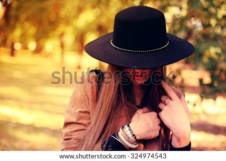 Street fashion concept - closeup portrait of a pretty girl. Wearing hat and suede jacket holding bag with fringe. Beautiful autumn woman. Soft warm vintage color tone. Artsy bohemian style. Outside #324974543