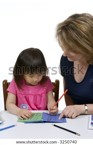 A young girl learns to write with the help of a teacher. #3250740