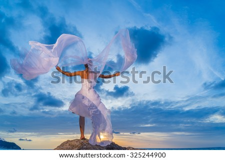 YOung bride by the sea at sunset in Greece #325244900