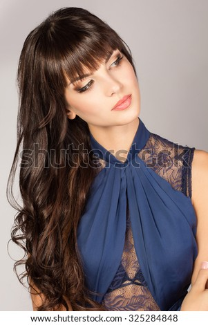 Awesome caucasian attractive sexy fashion model with long brunette natural hair, beautiful eyes, full lips, perfect skin posing in blue dress in studio for beauty photo shoot, retouched image