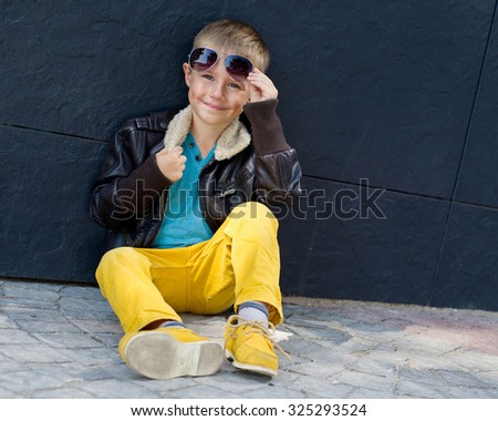 cute stylish boy in leather jacket sitting on the road Royalty-Free Stock Photo #325293524