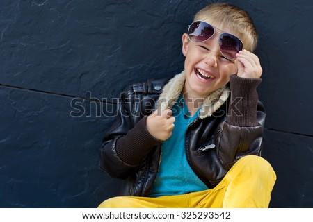 cute stylish boy in leather jacket sitting on the road Royalty-Free Stock Photo #325293542