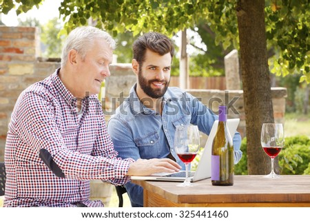 Portrait of senior and young winemaker sitting in front of laptop at wine cellar and tasting wines while working together on laptop. Small business.  #325441460