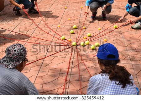 Team building activity, Tennis balls and table tennis balls with rope in harmonize activity #325459412