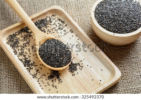 Chia seed on a wooden spoon against burlap background #325492370