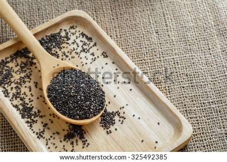 Chia seed on a wooden spoon against burlap background #325492385