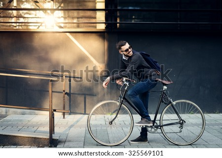 A young stylish businessman going to work by bike.  Royalty-Free Stock Photo #325569101