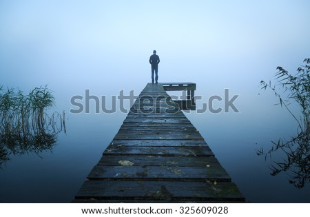 Depressed emotions concept: man standing at the end of a jetty, on a foggy, autumn morning. Royalty-Free Stock Photo #325609028