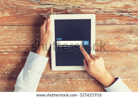 business, people, search, web and technology concept - close up of male hands using internet browser on tablet pc computer and coffee cup at table