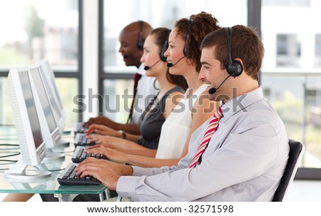 Smiling young businessman in a call center with his colleagues #32571598