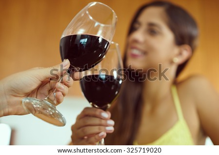 Two female friends at home, relaxing with a glass of red wine. The girls smile and celebrate making a toast. Focus on foreground #325719020