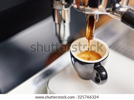 Professional espresso machine pouring strong looking fresh coffee into a neat ceramic cup #325766324