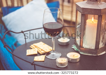 Glass of wine and candles on small iron table on the terrace or balcony. Toned picture