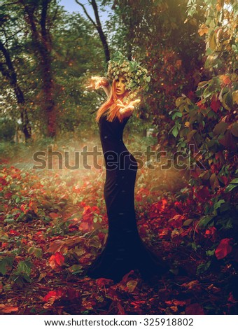 Vertical photo of adorable redhead witch conjures in the woods outdoors #325918802