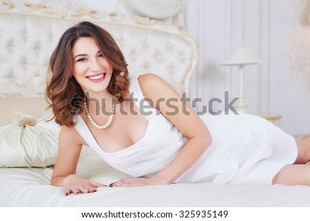 woman in a white dress in a bright bedroom. #325935149