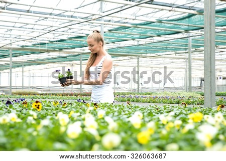 A young adult woman working in a gardening shop and carrying vegetables.  #326063687