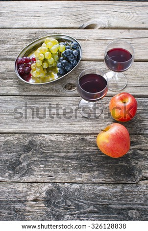 glasses of wine and apples, grapes on old wooden table #326128838