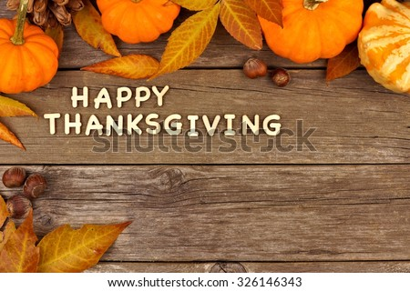 Happy Thanksgiving wooden letters with an autumn pumpkin and leaves corner border against old wood #326146343