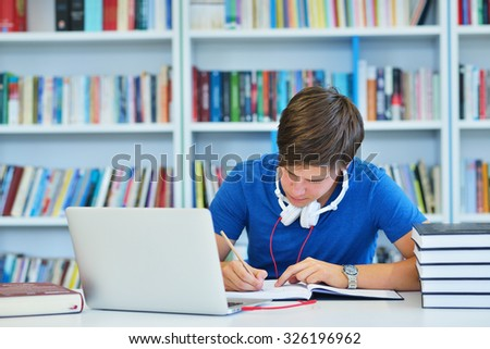 Smiling male student working in a library #326196962