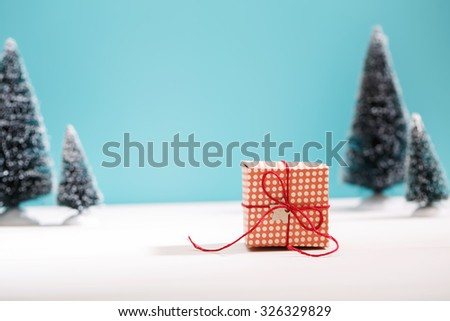 Little handmade gift box in a snow covered miniature evergreen forest