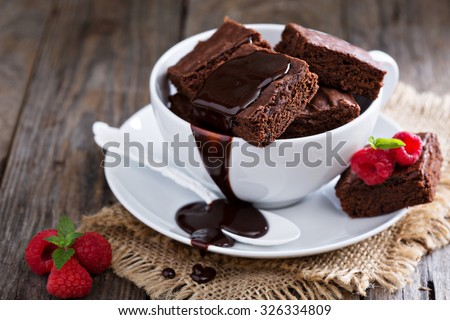 Brownies in stacked coffee cups with hot fudge chocolate sauce #326334809