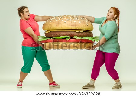 Funny picture of amusing, chubby women on white background.  Two women holding a huge sandwich