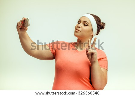 Funny picture of amusing chubby woman on white background. Woman smiling and taking a selfie