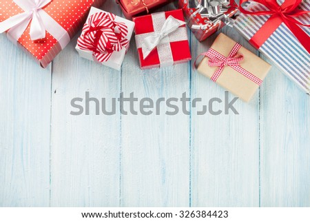 Christmas gift boxes on wooden table with snow. Top view with copy space #326384423