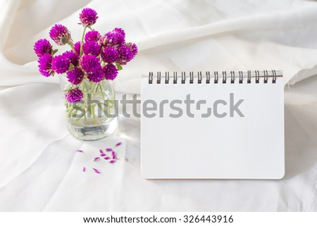 notebook or calendar with violet flower on table morning concept.