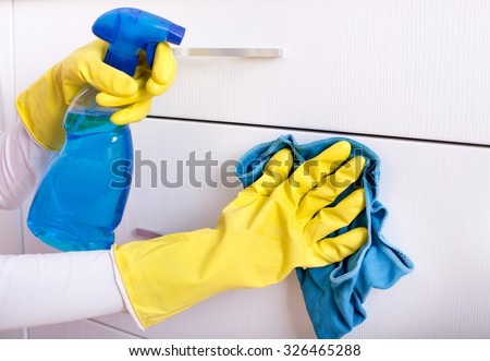 Close up of female hand with rubber gloves and detergent in sprayer cleaning drawers #326465288