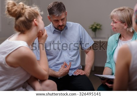 Businessman talking about his problems during group therapy session #326495141