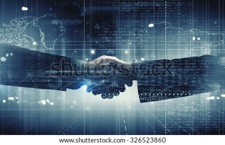 Close up of business handshake on digital background Royalty-Free Stock Photo #326523860