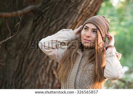 Beautiful woman in a knitted garment wears a cap in the park #326565857