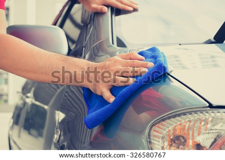 A man hand cleaning car with microfiber cloth #326580767