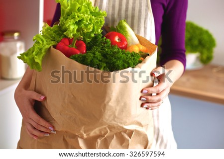 Young woman cutting vegetables in the kitchen #326597594