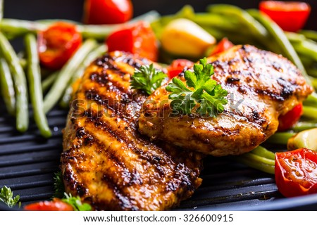 Grilled chicken breast in different variations with cherry tomatoes, green French beans, garlic, herbs, cut lemon on a teflon pan. Royalty-Free Stock Photo #326600915