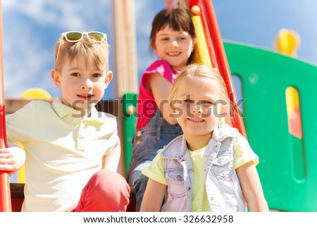 summer, childhood, leisure, friendship and people concept - group of happy kids on children playground #326632958