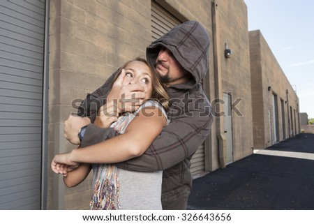 SELF DEFENSE | A young woman sees a suspicious person walking behind her and plans to defend herself against a male attacker in an alley.    Royalty-Free Stock Photo #326643656
