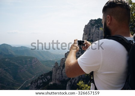 Young male tourist in white t-shirt takes photos with smart phone on peak of rock #326657159