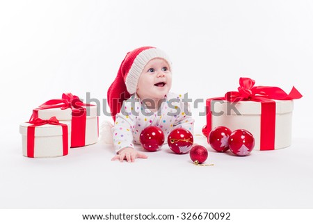 Cute baby lying on his stomach in a New Year's cap among Christmas balls and red box with presents and looking at the camera with a smile on his face, picture with depth of field