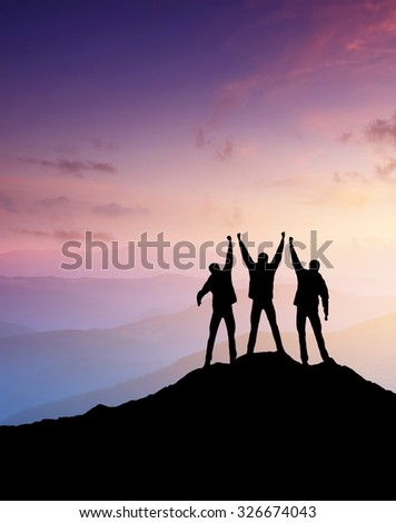 Silhouettes of team on mountain peak. Sport and active life concept #326674043