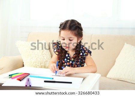 Cute little girl drawing picture on home interior background #326680433