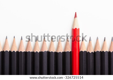 Red pencil standing out from crowd of plenty identical black fellows on white table. Leadership, uniqueness, independence, initiative, strategy, dissent, think different, business success concept Royalty-Free Stock Photo #326725514