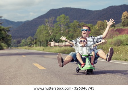 Father and son playing  on the road at the day time.  Concept of friendly family. Royalty-Free Stock Photo #326848943