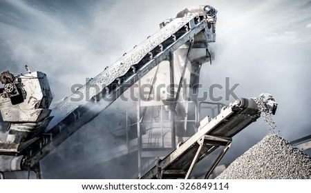 Cement production factory on mining quarry. Conveyor belt of heavy machinery loads stones and gravel  Royalty-Free Stock Photo #326849114