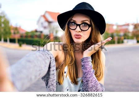 Hipster stunning woman making selfie , sending kiss, surprised funny emotions, natural make up, long blonde hairs, hipster hat and glasses, amity time, countryside. #326882615